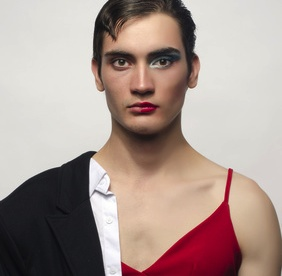 Half man, half woman, wearing a black suit and a red dress.