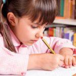 Cute little girl in uniform doing calligraphy exercises.