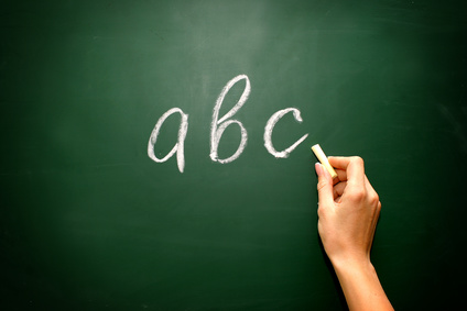 abc letters and chalk with woman hand on blackboard